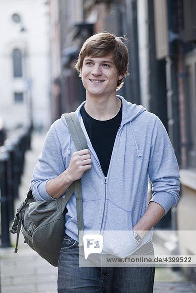 Junger Mann geht und lächelt