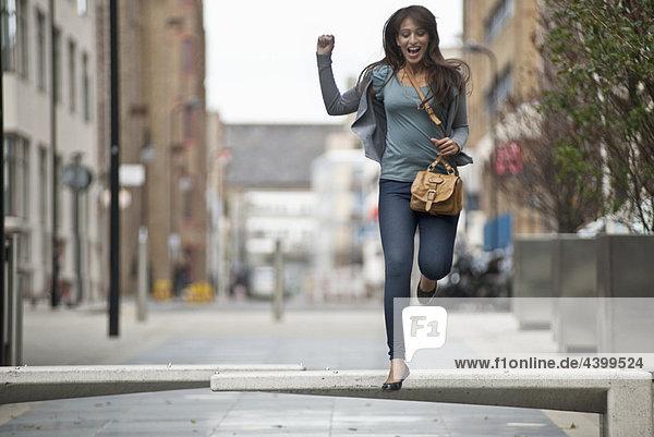 Junge Frau beim Springen auf der Straße