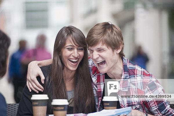 Paar am Kaffeetisch sitzend  lachend
