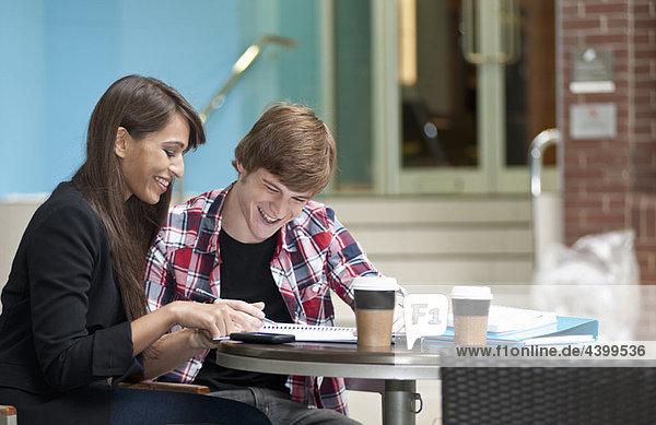 Pärchen  das am Kaffeetisch sitzt und sich Notizen macht.
