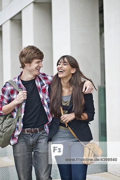 Ein Paar  das auf der Straße spazieren geht und lacht.