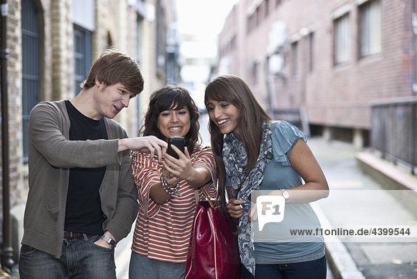 Freunde teilen sich das Handy in der Straße