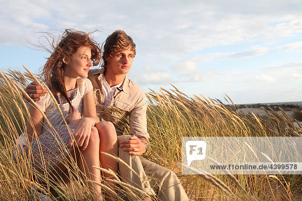 Young couple in the dunes at sunset