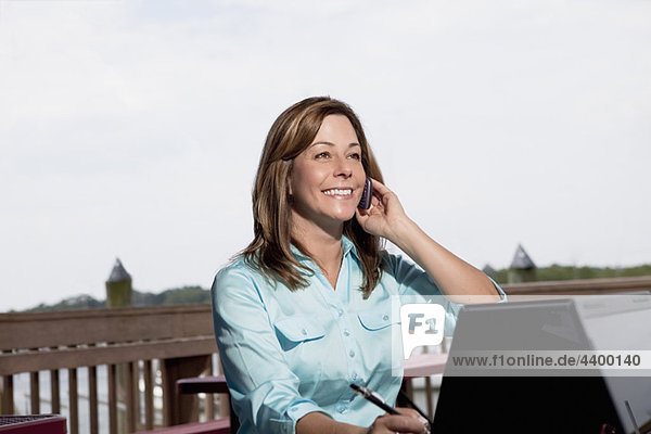 Woman on cell phone with laptop