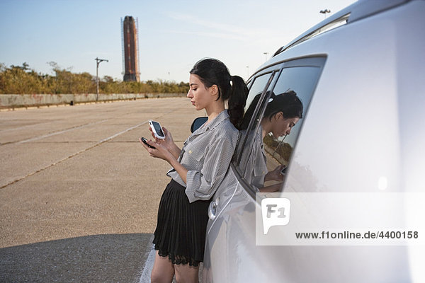 Mädchen am Telefon und PDA mit dem Auto