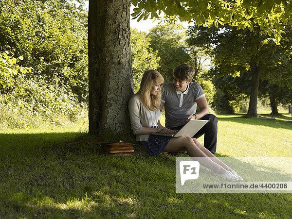 Boy helping a girl under a tree