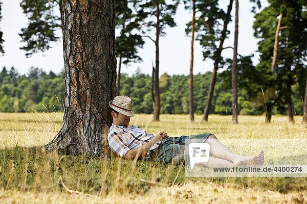 Porträt jungen Mannes dösen unter Baum im Sommer