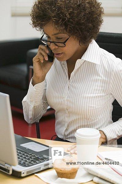 Frau im Büro mit Muffin und Tasse Kaffee