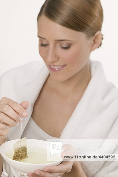 Frau mit weißen Tuch und Schüssel Tee