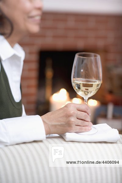 Woman on sofa holding glass of white wine