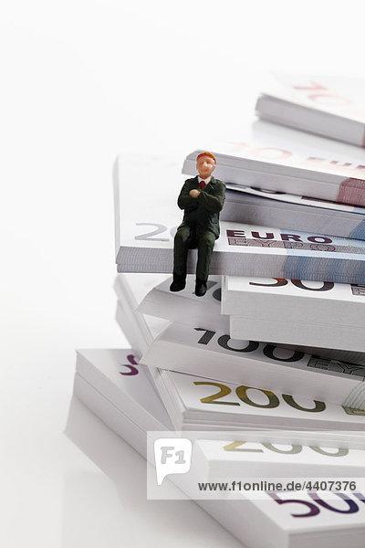 Managerfigur auf Euro-Banknotenstapel sitzend