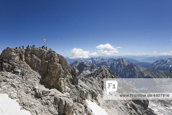 Österreich  Tirol  Zugspitze  Menschen und Kreuz auf Berggipfel