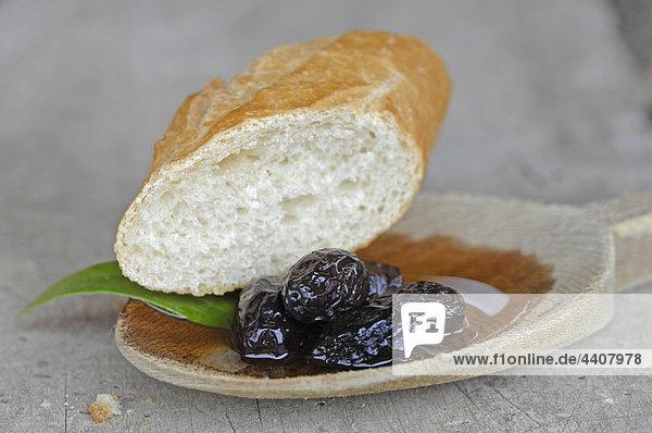 Schwarze Oliven und Weißbrot in Holzlöffel  Nahaufnahme.
