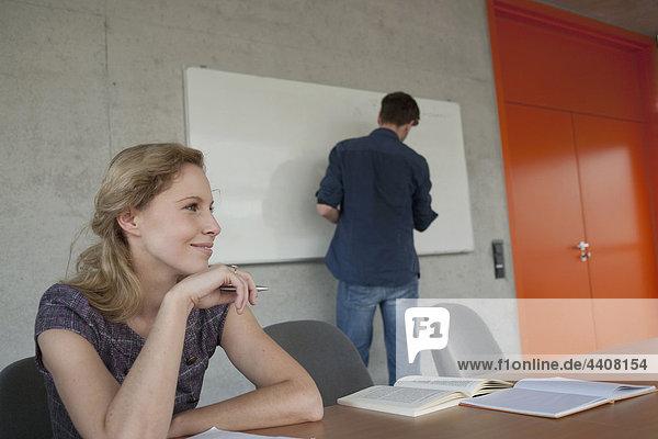 Frau lächelnd mit Mann auf Zeichenbrett im Hintergrund