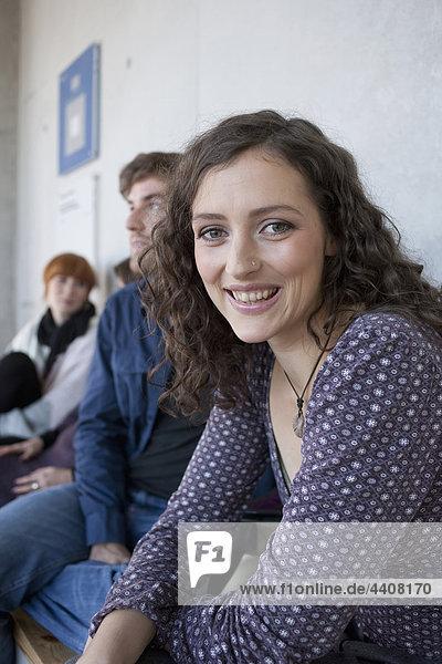 Frau lächelt mit Studenten im Hintergrund