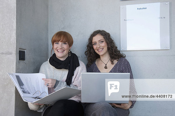Germany  Leipzig  University students using laptop  smiling  portrait