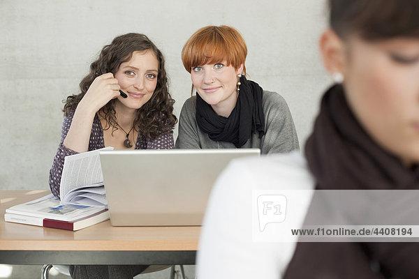 Deutschland  Leipzig  Studenten mit Laptop  lächelnd