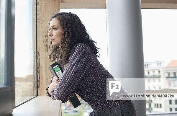 Junge Frau hält die Akte und schaut durchs Fenster.