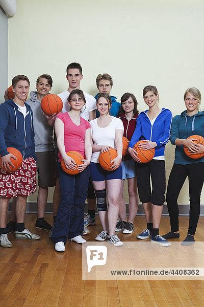 Deutschland  Berlin  Menschen stehen und halten Basketball  Portrait