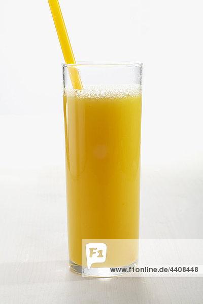 Glas Orangensaft mit Stroh auf weißem Grund