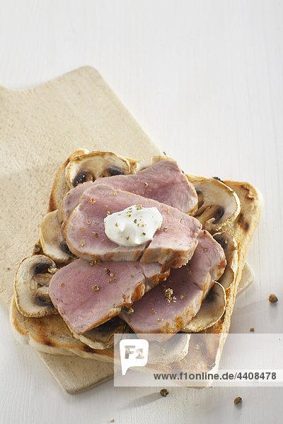 Schweinefilet-Sandwich mit Champignons und Crème fraîche auf weißem Grund  Nahaufnahme