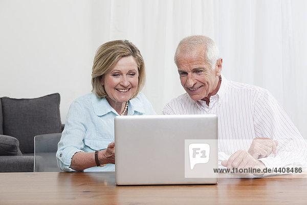 Senior Paar mit Laptop  lächelnd
