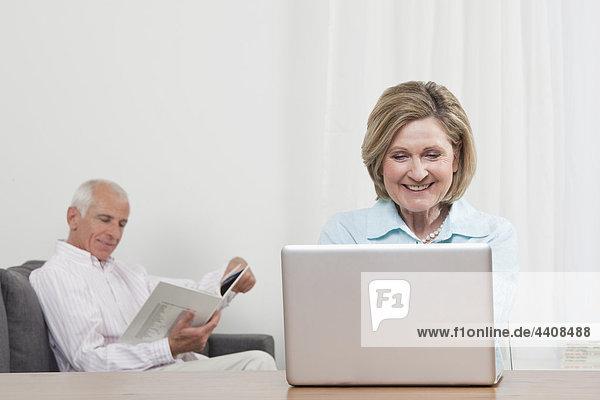 Frau mit Laptop und Mann im Hintergrund