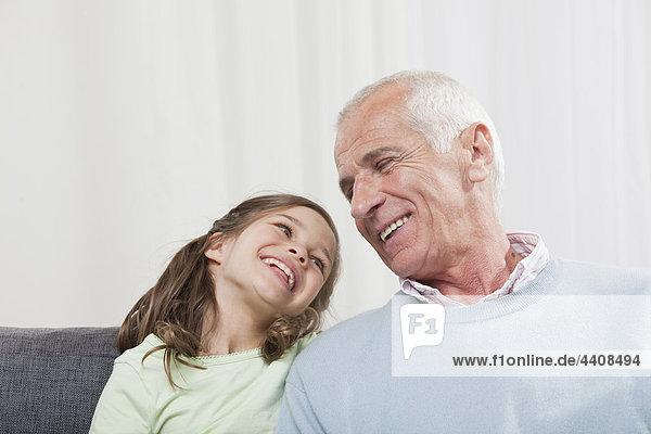 Großvater und Enkelin (6-7) schauen sich an und lächeln.