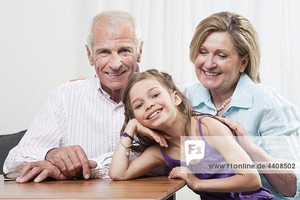 Enkelin (6-7) Kopf in Hand mit den Großeltern  lächelnd