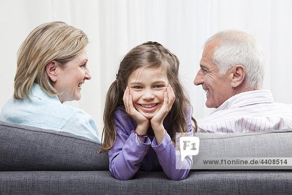 Enkelin (6-7) lächelnd mit Kopf in der Hand und Großeltern im Hintergrund