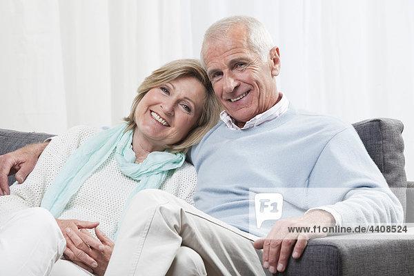 Seniorenpaar auf Couch sitzend  lächelnd  Portrait
