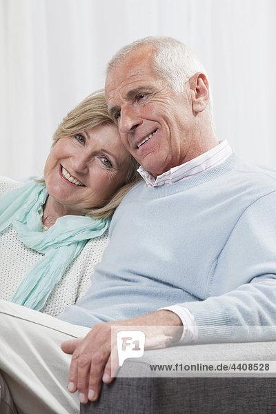 Seniorenpaar auf der Couch sitzend  lächelnd
