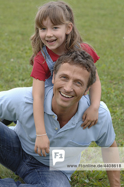 Father and Daughter playing in garden  portrait  smiling.