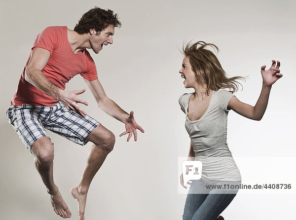 Mann und Frau schreien und springen vor grauem Hintergrund