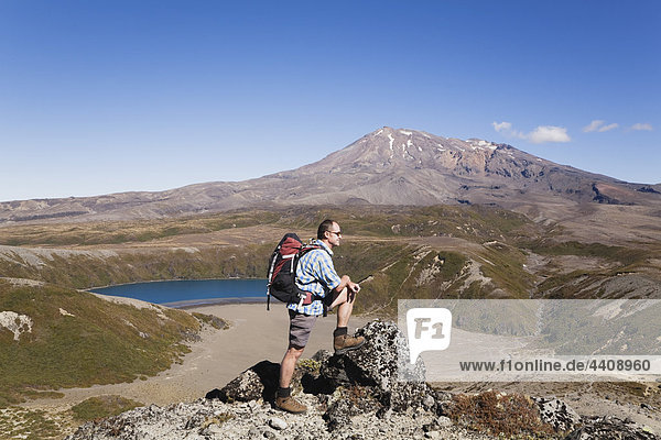 New Zealand  North Island  Man hiking at tongariro national park with mount ruapehu in background