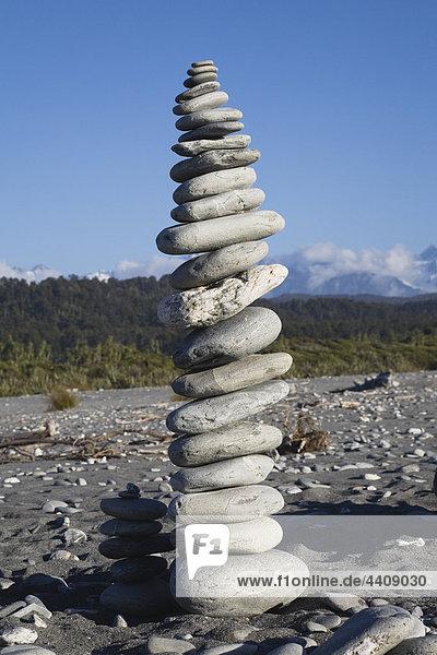Neuseeland  Südinsel  Westküste  Steinhaufen am Strand mit Bergen im Hintergrund