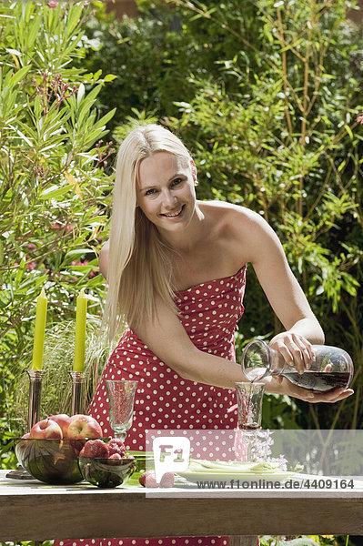 Österreich  Frau gießt Wein ins Glas  lächelnd