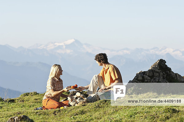 Young couple sitting face to face sharing breakfast.