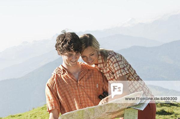 Ein junges Paar  das lächelnd auf eine Karte auf einem Berggipfel schaut.