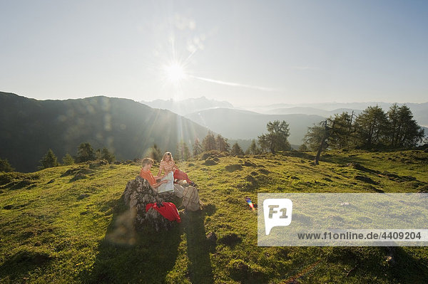 Ein junges Paar  das sich eine Karte auf einem Berggipfel ansieht.
