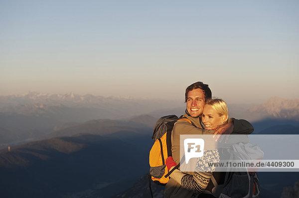 Österreich  Steiermark  Dachstein  Junges Paar umarmt den Berggipfel  lächelnd