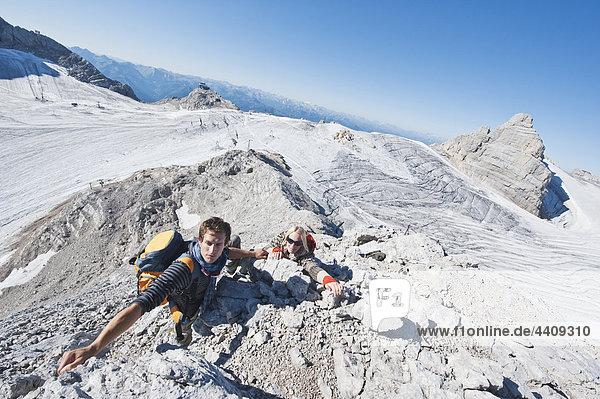 Austria  Steiermark  Dachstein  Young couple climbing rock