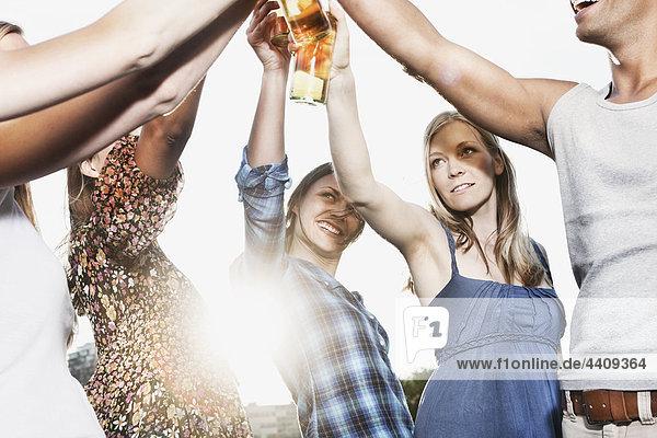 Mann und Frau rösten Bierflaschen.