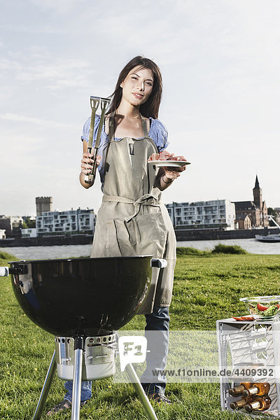 Young woman barbecueing  portrait