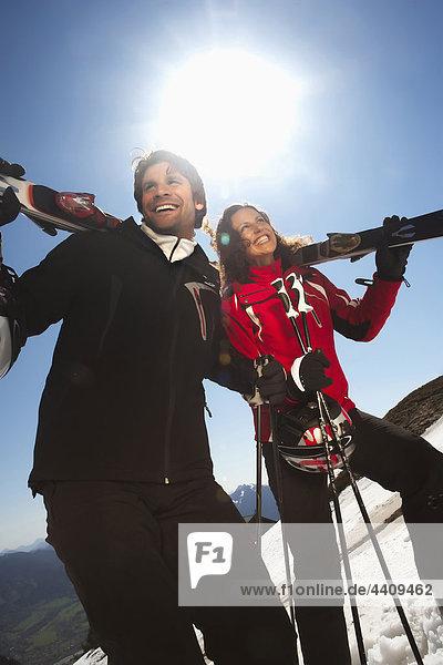 Italien  Südtirol  Paar mit Skiern  wegschauen  lächeln