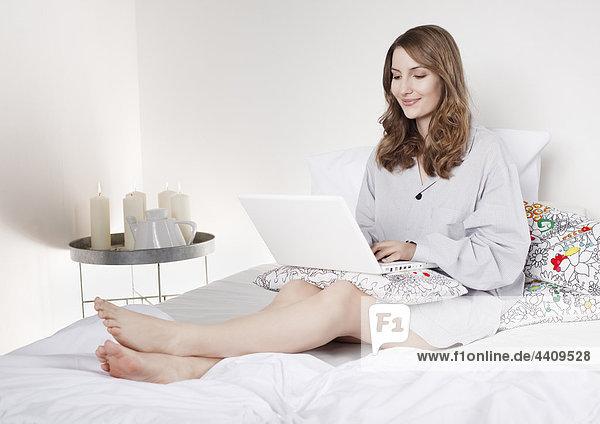 Frau auf dem Bett sitzend und mit Laptop  lächelnd