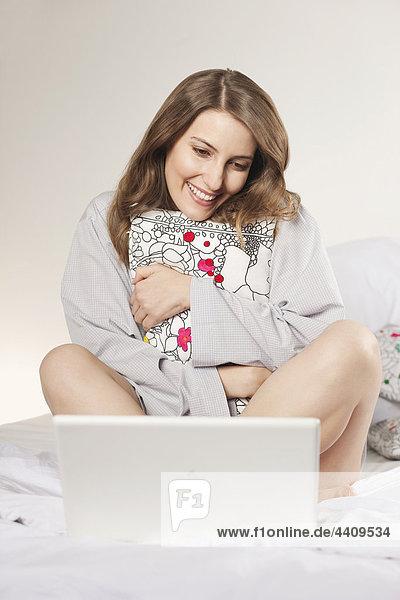 Frau sitzend auf dem Bett mit Kissen und mit Laptop