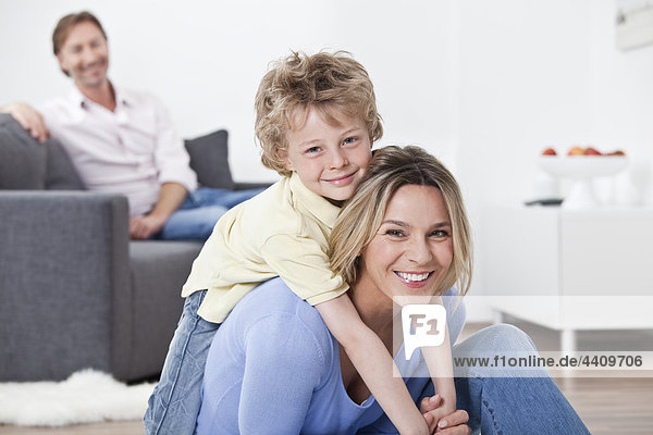 Mutter und Sohn lächeln mit Vater im Hintergrund