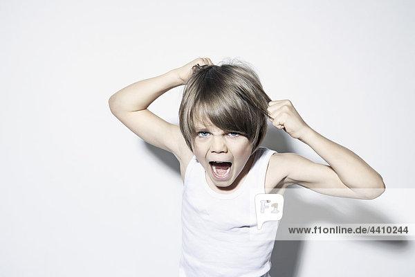 Junge (8-9) beim Haareziehen und Schreien  Portrait