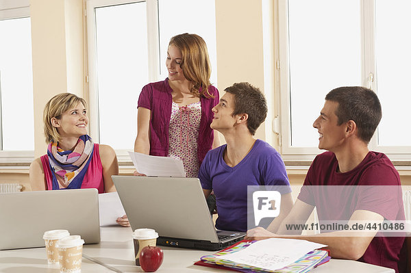 Deutschland  Emmering  Studenten mit Laptop mit Einwegbecher und Apfel auf dem Tisch
